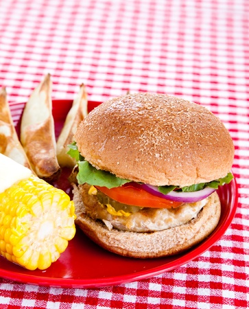 Delicious healthy turkey burger on a whole grain bun, with baked potato wedges and corn on the cob.   photo
