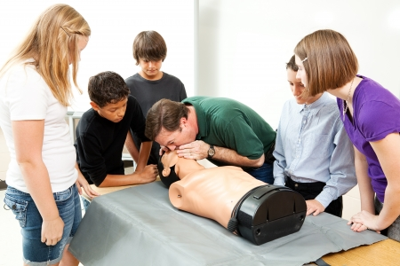 High school health class instructor demonstrates CPR lifesaving techniques for his students.   photo