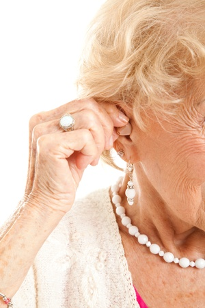 listening device: Closeup of a senior womans hand inserting a hearing aid in her hear.   Stock Photo