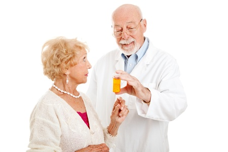 doctor holding pills: Pharmacist giving dosage instructions to an attractive senior patient.  Isolated on white.