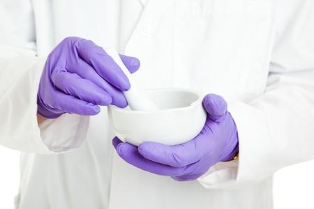 mortero: Detalle de las manos de un farmacéutico o científico, sosteniendo un mortero y pilón y con guantes de goma.