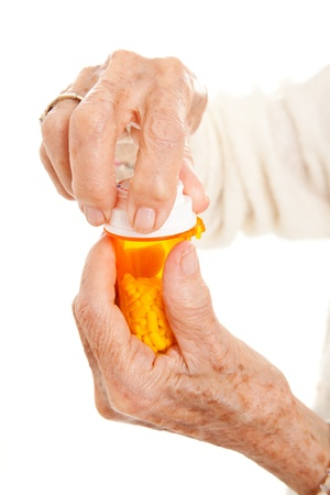 Closeup of senior woman's hands trying to open a prescription bottle with childproof cap.  Isolated on white. Stock Photo - 10415861