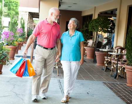 seniors walking: Senior woman on a shopping spree looks up at her handsome husband whos carrying her bags.   Stock Photo