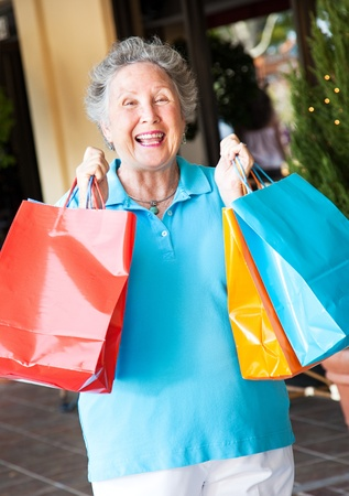 shopping center: Senior on a shopping trip, excited about her bargains.   Stock Photo