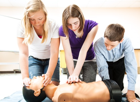 cardiopulmonary: Students practicing CPR life saving techniques on a mannequin.   Stock Photo
