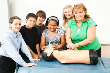 chest compression: Group of students and their teacher, learning CPR in school.