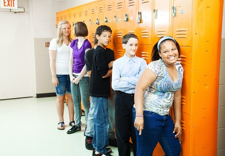 socializing: Diverse group of teenage students at their school lockers between classes.