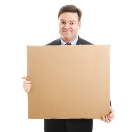 Embarrassed jobless businessman holding up a blank cardboard sign.  Isolated on white.