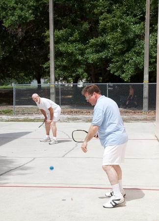 racquetball: Hijo de padre y adulto jugar r�quetbol al aire libre.