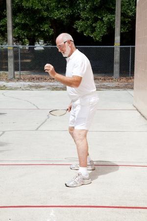 racquetball: Ajustar alto hombre jugar r�quetbol en un tribunal p�blico.