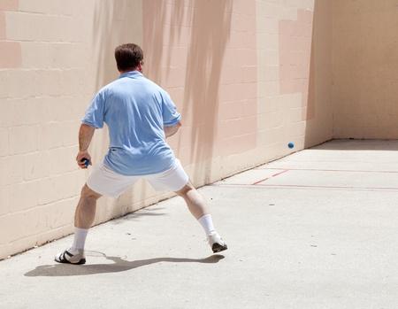 mid adult man: Hombre de mediana edad jugar al tenis en una cancha p�blica.