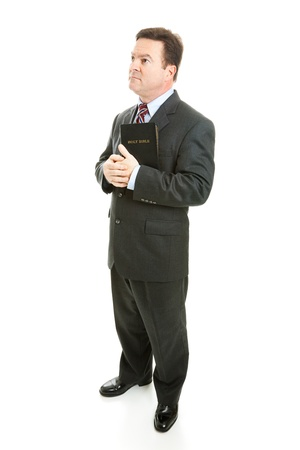 thoughful: Pious minister or businessman holding his bible and looking thoughful.  Full body isolated on white.   Stock Photo