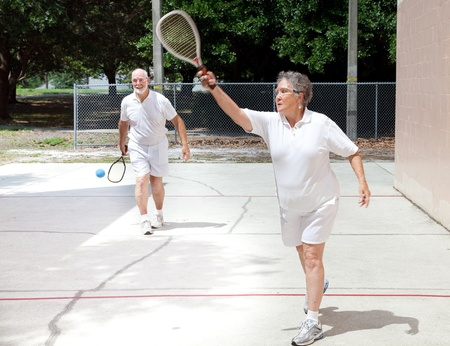 Active senior couple playing racquetball on a public court. photo