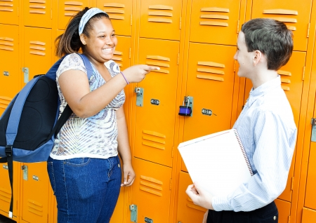 corridors: Middle school boy and girl laughing and joking together by their lockers.   Stock Photo