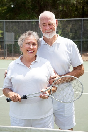 Active senior couple on the tennis courts. Stock Photo - 10529292
