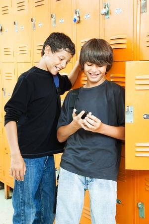 Teenage boys playing video games between classes in school.   photo