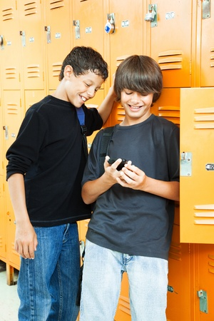 misbehaving: Teenage boys playing video games between classes in school.