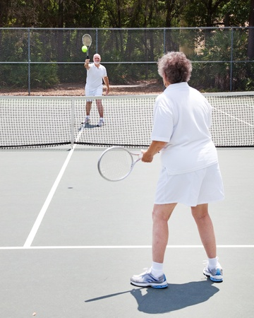 jugando tenis: Pareja senior activa jugar juntos al tenis en una cancha al aire libre
