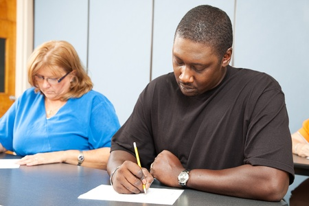 Diverse adult education students taking a test in class.