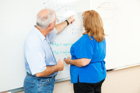 overweight students: Adult education student working math equations on the board, with her teachers help.   Stock Photo