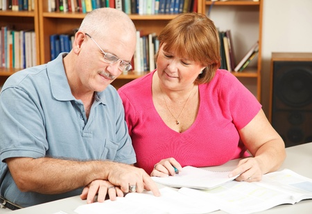 adult learning: Adult students studying together in the library.   Stock Photo