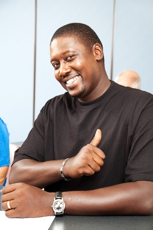 Handsome african-american adult college student gives thumbs up.   Stock Photo - 12029584