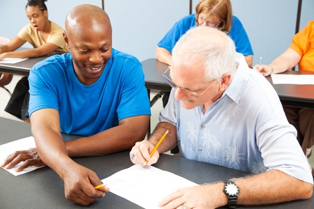 education help: Younger college student tutors mature older student who is struggling to keep up.  Focus on the tutor.