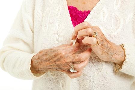 artritis: Manos artríticas mujer mayor lucha por botón de su chaqueta.