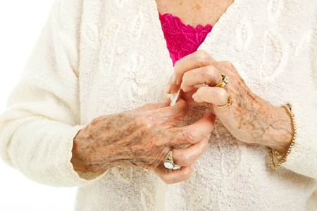 arthritis: Senior womans arthritic hands struggling to button her sweater.   Stock Photo