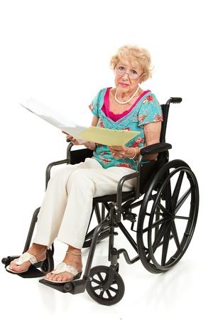 Senior vrouw in een rolstoel met een stapel rekeningen. Volledig lichaam op wit wordt geïsoleerd. Stockfoto