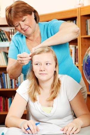 overweight students: Mother fixing teenage daughters hair, as the girl tries to study.  Focus on the mother.