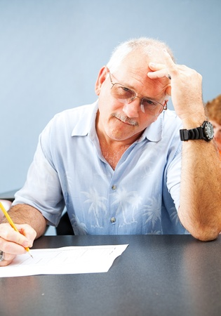 Middle aged man goes back to college and experiences frustration with the learning process.   Stock Photo - 12029580