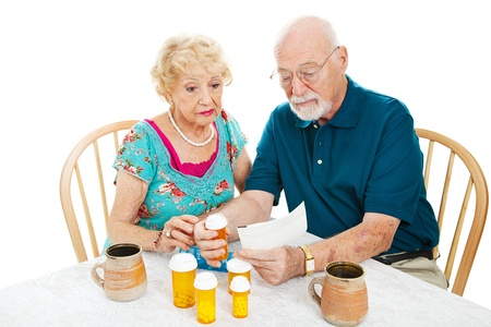 pill box: Senior couple reading instructions from the pharmacy on how to take their medication. White background.   Stock Photo