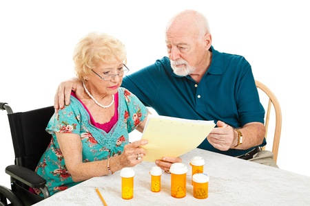 Disabled senior woman and her husband go over their medical and prescription drug bills.  Isolated on white.   photo