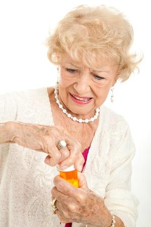 artritis: Superior de la mujer luchando para abrir una tapa a prueba de ni�os en su botella de la prescripci�n. Blanco fondo.