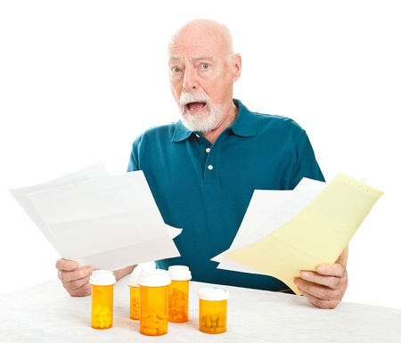 medical bill: Senior man overwhelmed by the cost of his medical care and prescription drugs.  White background.