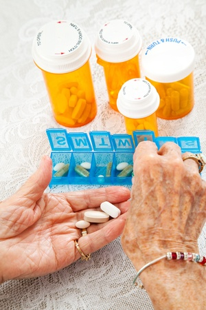 sorting: Closeup of an elderly womans hands sorting her medication for the week.