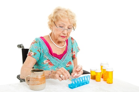 Senior woman in a wheelchair, couting out her pills for the week.  White background. photo