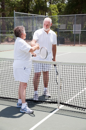 Active senior couple shakes hands over the tennis net.   photo