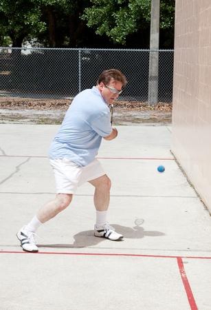 racquetball: Hombre de mediana edad jugando a un juego feroz de racquetball.