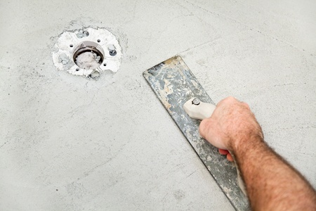 smoother: Using a float to smooth concrete during a bathroom remodel project.  Room for text.