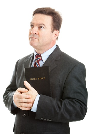 holy bible: Religious Christian man in a business suit, holding his bible and looking heavenward.  Isolated on white.