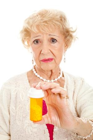 rx: Sad senior woman holding a bottle of pills.  White background.