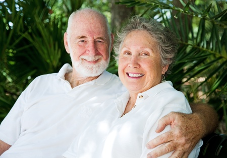 hugging couple: Affectionate senior couple in tennis whites, against a background of tropical palm fronds.