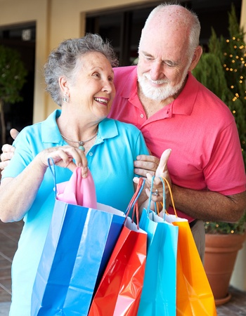 Senior man looks in the shopping bags to see what his wife has bought.   photo
