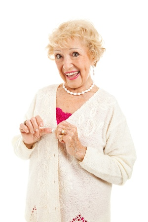 medical dressing: Senior lady buttons her sweater successfullly without any arthritis pain.  Isolated on white.