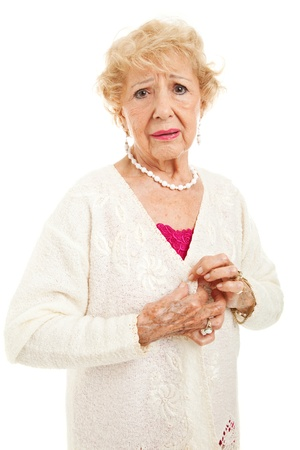 rheumatism: Senior woman with painful arthritis unable to button her sweater.  Isolated on white.   Stock Photo