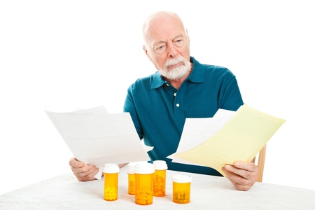 Senior man depressed by a pile of medical bills.  Isolated on white.   photo