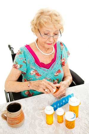 Disabled senior woman in a wheelchair, counting out her medications for the week.  White background.   photo