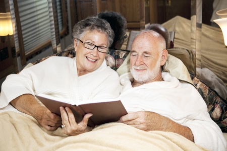 Senior couple reads together at bedtime, in their motor home.   photo